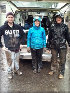 Three volunteers standing in rain