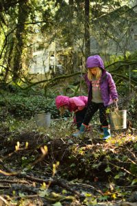 2 young children planting natives.