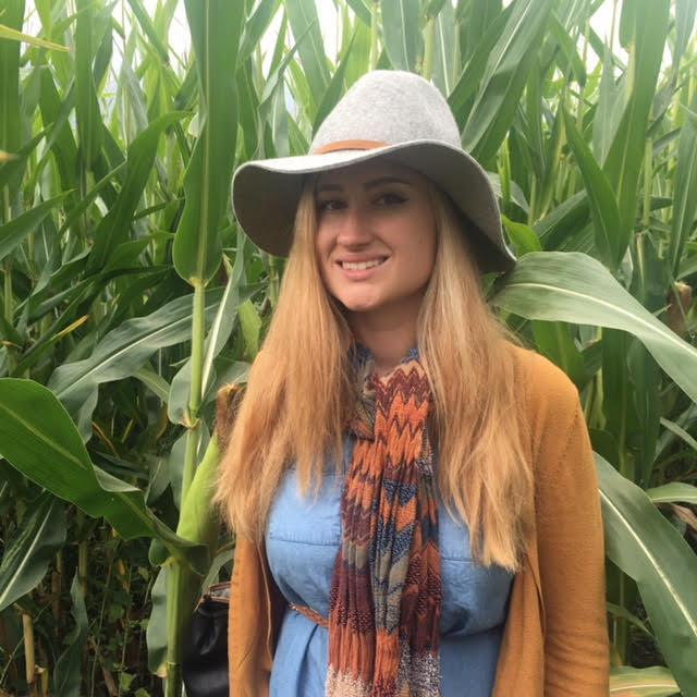 Jackie Brenner standing in a corn field.